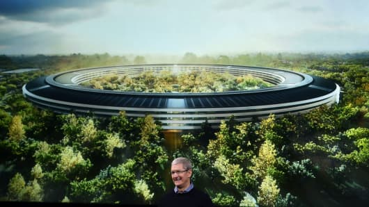 Apple CEO Tim Cook stands in front of a slide of the company's new campus which is under construction during a media event at Apple headquarters in Cupertino, California