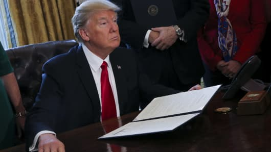 President Donald Trump signs Executive Orders in the Oval Office of the White House, including an order to review the Dodd-Frank Wall Street to roll back financial regulations of the Obama era February 3, 2017 in Washington, DC.