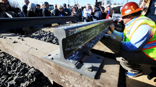 Invited guests sign segments of railroad track during a groundbreaking ceremony for a bullet train station in Fresno on Tuesday, Jan. 6, 2015.