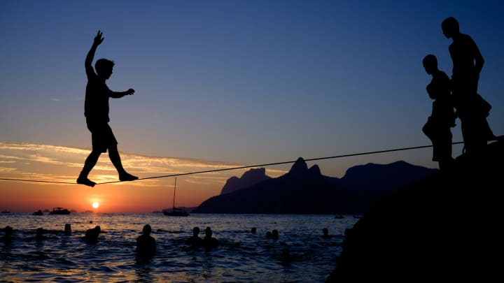 A man crosses on a slickline installed over the water during sunset at Apoador beach in Rio de Janeiro, Brazil