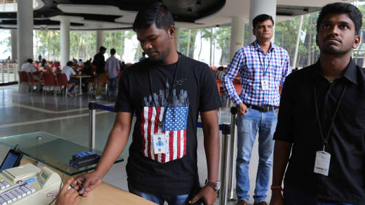 An Infosys employee sports a t-shirt featuring a U.S. flag as he buys coupons for lunch while others wait for their turn at company's headquarters in Bangalore, India.