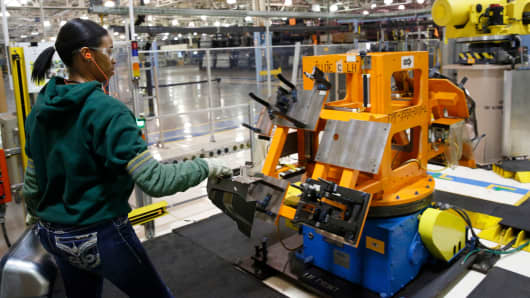 An auto worker assembles parts that will be welded by a robot for the Dodge Dart rear wheel house at Fiat Chrysler Automobiles NV's Warren Stamping Plant in Warren, Michigan.
