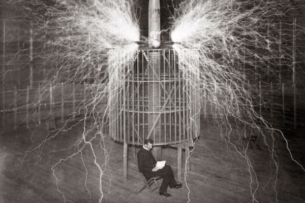 Nikola Tesla sitting in his Colorado Springs laboratory with his 'Magnifying transmitter' in 1899.