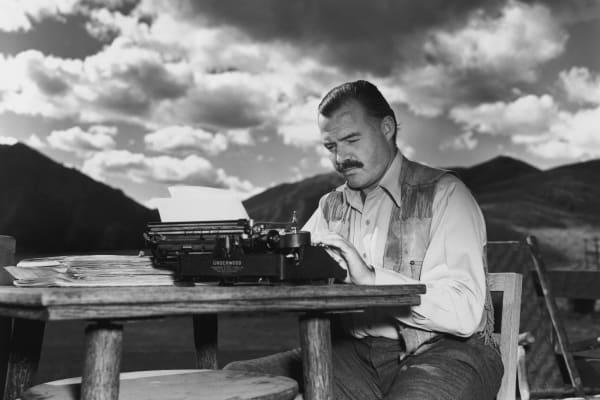 American writer Ernest Hemingway (1899 - 1961) works at his typewriter while sitting outdoors, Idaho. Hemingway disapproved of this photograph saying, 'I don't work like this.'
