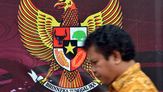 A pedestrian walks past the Indonesian symbol of Garuda Pancasila (back), a mythical golden eagle with a heraldic shield on its chest.