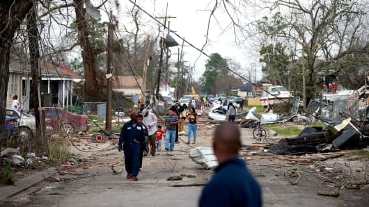 Residents walk down a street along Chef Menture Ave after a tornado touched down in the eastern part of the city on February 7, 2017 in New Orleans, Louisiana.