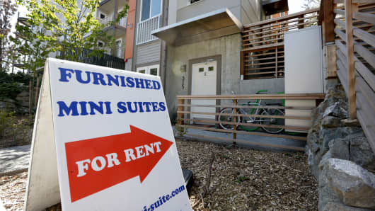 A sign points toward a building renting tiny apartments in Seattle.