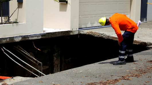 A worker inspects a sinkhole that appeared after heavy rain outside a property located near Australian Prime Minister Malcolm Turnbull's residence in Sydney, Australia, February 8, 2017.