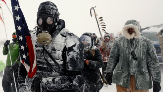 "A man takes part in a march with veterans to Backwater Bridge just outside of the Oceti Sakowin Camp during a snow fall as ""water protectors"" continue to demonstrate against plans to pass the Dakota Access pipeline adjacent to the Standing Rock Indian Reservation, near Cannon Ball, North Dakota, December 5, 2016."