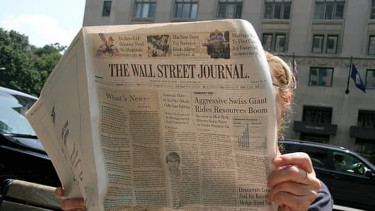 A person reading the Wall Street Journal newspaper