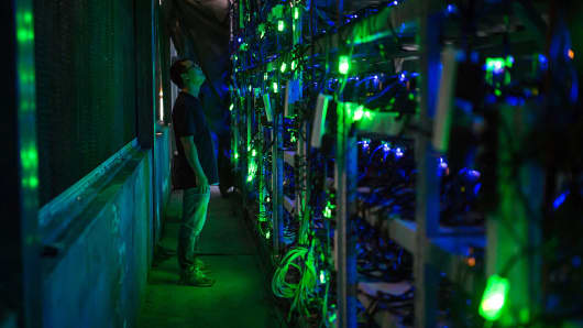 A HaoBTC bitcoin mine site manager checks mining equipment inside their bitcoin mine near Kongyuxiang, Sichuan, China.
