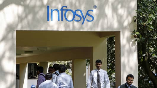 Employees walk below the Infosys logo at the company's campus in Electronics City in Bangalore, India.