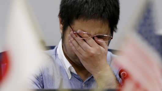 An employee of a foreign currency company wipes his face in a dealing room in Tokyo, Japan, Apr. 7, 2016.