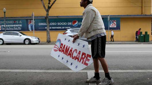 A man holds a sign directing people to an insurance company where they can sign up for the Affordable Care Act, also known as Obamacare.