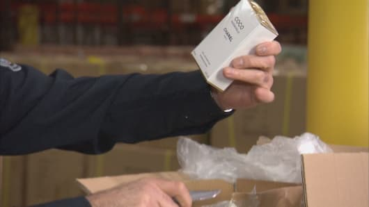 A government agent inspecting a shipment finds a bottle of what is believed to be counterfeit Chanel perfume.