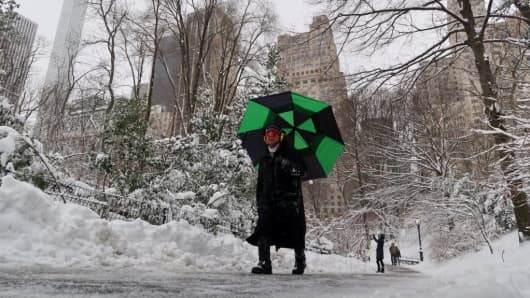 People walk through Central Park during a snowstorm.