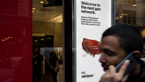 A pedestrian talks on a mobile device while walking past a Verizon store in San Francisco.
