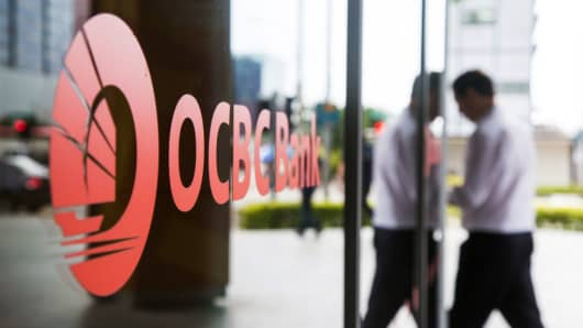 A man walks past an OCBC branch in the central business district of Singapore.