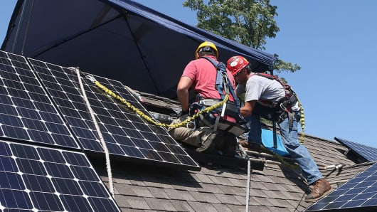 Workers install Solar Service solar electric panels on the roof of a home.