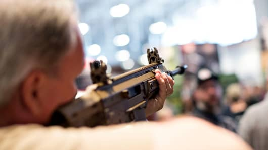 An attendee sights a rifle in the Remington Arms booth on the exhibition floor of the 144th National Rifle Association (NRA) Annual Meetings and Exhibits at the Music City Center in Nashville, Tennessee, U.S., on April 11, 2015.