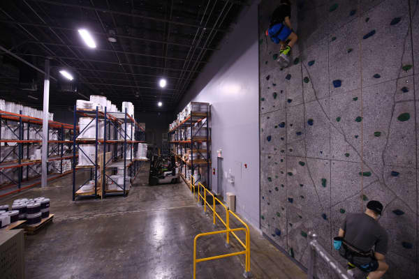 "There is a climbing wall inside the new Popular Ink production facility. ""Much like Google we realize we spend more time with each other than we do our families. Thus our campus is fun and interactive,"" says Riess."
