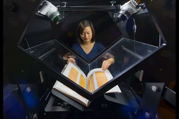 Lan Zhu, a scanner at the Internet Archive, digitizing books on the Tabletop Scribe, the scanner they designed to process millions of books around the world.