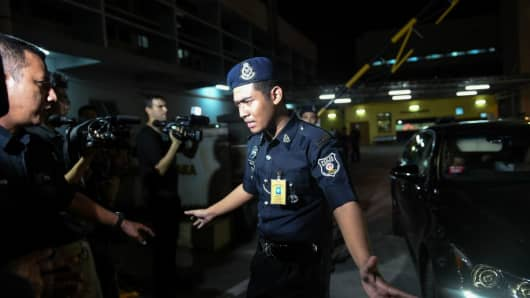 A Malaysian policeman (C) tries to stop members of the media as a North Korean embassy official leaves the Forensic department where the body of a North Korean man suspected to be Kim Jong-Nam, half-brother of North Korean leader Kim Jong-Un, is being kept at the Hospital Kuala Lumpur in Kuala Lumpur on February 15, 2017.