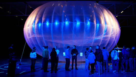 Visitors stand next to a high altitude WiFi internet hub, a Google Project Loon balloon, on display at the Air Force Museum in Christchurch, New Zealand, on June 16, 2013.