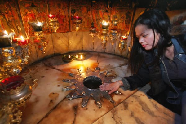 A pilgrim lays her hand on the silver star in the Grotto under the Church of the Nativity, which according to tradition marks the sport Jesus was born.
