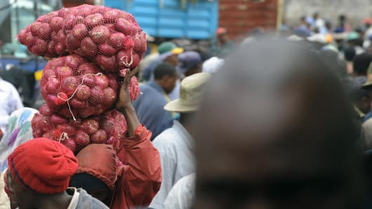 A Kenyan man carries a bag of onions at the Marikiti market in Nairobi