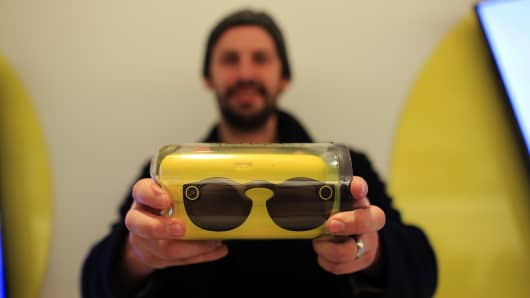 A customer displays a pair of Snapchat Spectacles by Snap Inc. for a photograph inside the company's pop-up store in New York, U.S., on Monday, Dec. 5, 2016.