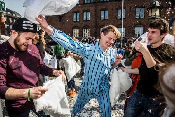 People fight with pillows during World Pillow Fight Day in front of the City Hall in Copenhagen, Denmark April 2, 2016.
