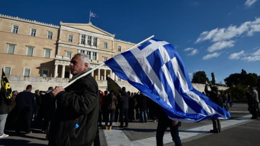 A farmer holds a Greek flag in front of parliament during a protest against the government's tax and social security reforms on February 14, 2017 in Athens, Greece.