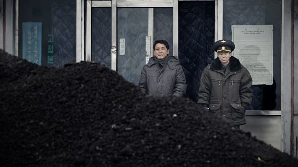 his picture taken on December 14, 2012 from China's northeastern city of Dandong, looking across the border, shows a North Korean military officer (R) and a North Korea man (L) standing behind a pile of coal along the banks of the Yalu River in the northeast of the North Korean border town of Sini