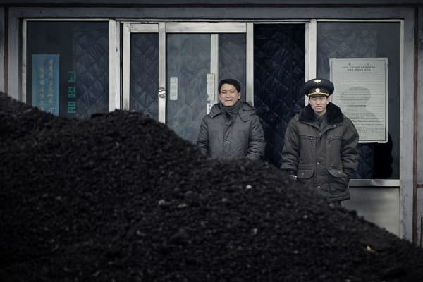 his picture taken on December 14, 2012 from China's northeastern city of Dandong, looking across the border, shows a North Korean military officer (R) and a North Korea man (L) standing behind a pile of coal along the banks of the Yalu River in the northeast of the North Korean border town of Siniuju.