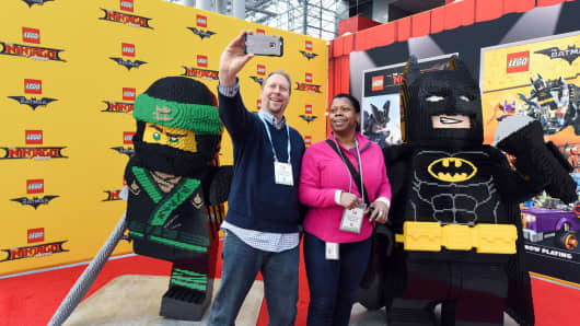 Attendees take a selfie with life-size LEGO models of Lloyd, star of The LEGO NINJAGO Movie, and box-office hero Batman at the North American International Toy Fair, Saturday, Feb. 18, 2017, in New York.