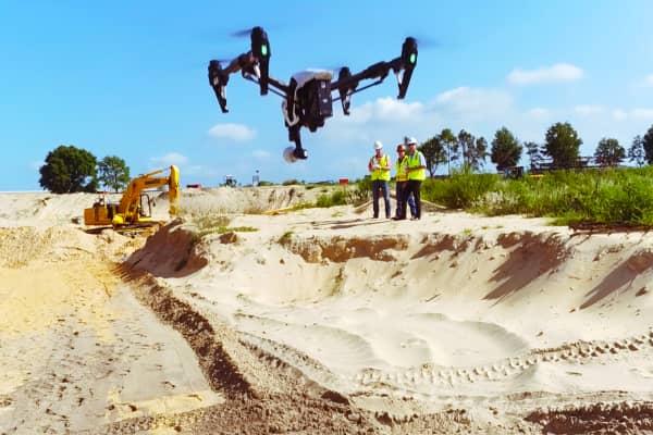Contractors fly drone using DroneDeploy's app.