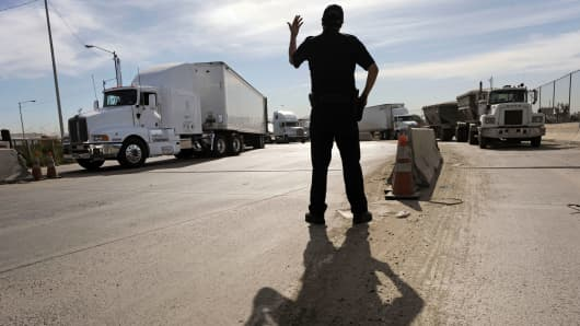 U.S. Customs and Border Protection officer directs trucks entering the United States from Mexico through the Otay Mesa Port of Entry in San Diego, California.
