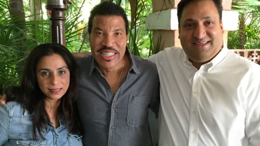 Celebrity investor Lionel Richie with Dr. Renee Dua (left) and Nick Desai (right), husband and wife co-founders of health care on-demand app Heal.
