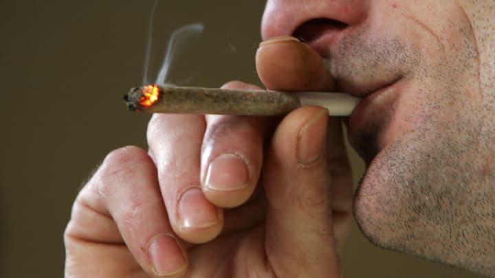 A man smokes a cigarette of marijuana.