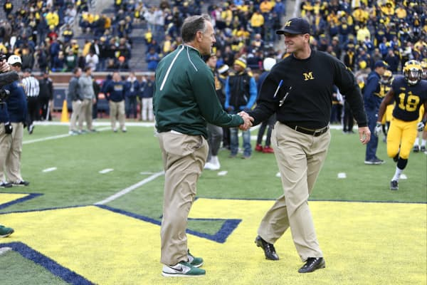 Head coach Mark Dantonio of the Michigan State Spartans and Head coach Jim Harbaugh of the Michigan Wolverines shake hands.