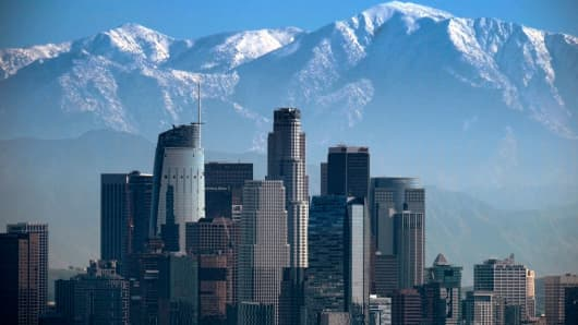 Snow covered mountain tops rise behind downtown Los Angeles last month.