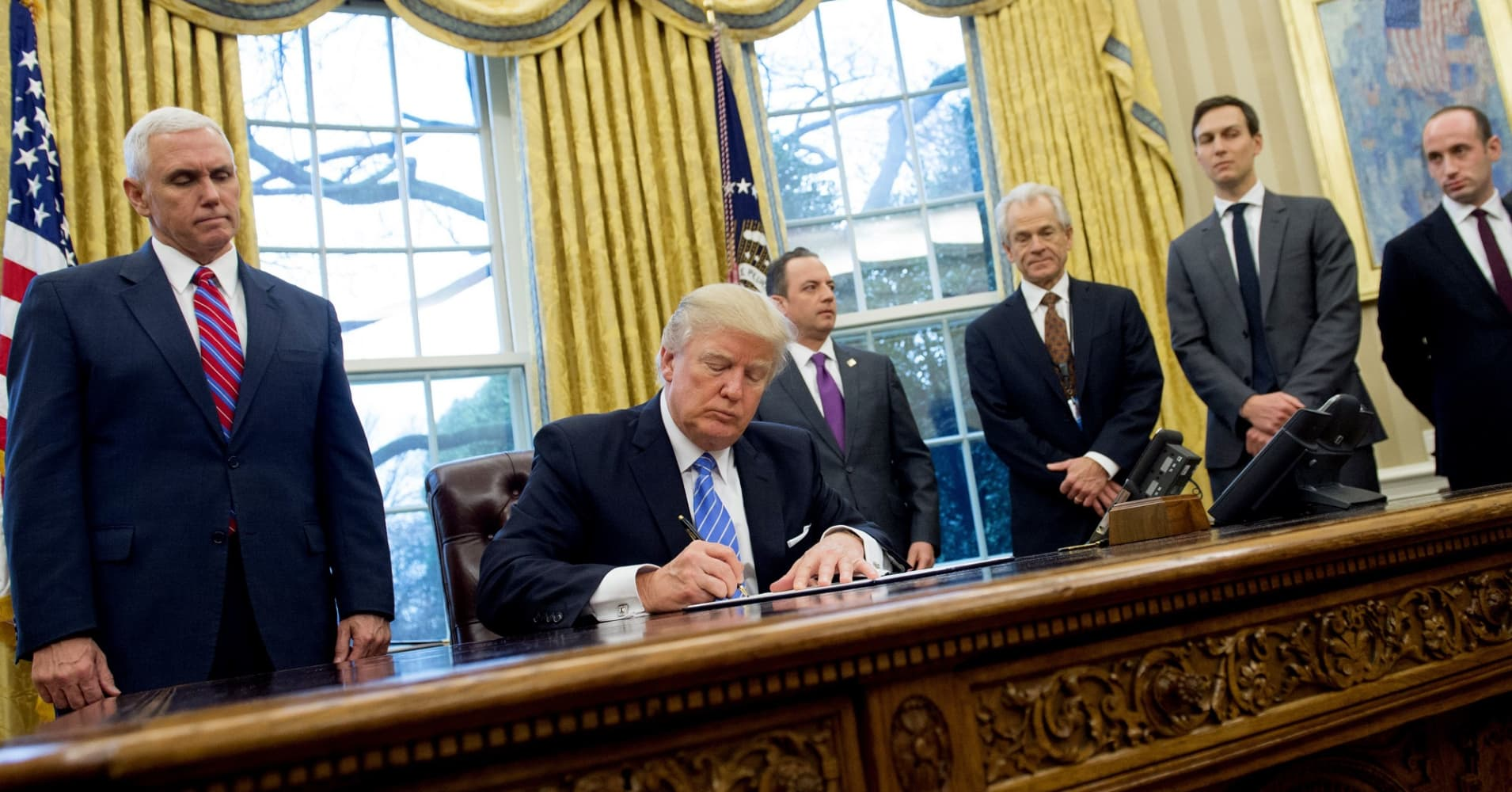 President Donald Trump signs an executive order alongside White House Chief of Staff Reince Priebus (C), US Vice President Mike Pence (L), National Trade Council