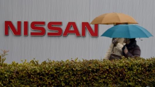 People walk past the logo of Japan's auto giant Nissan Motor at the company's headquarters in Yokohama, in suburban Tokyo, on February 9, 2017.