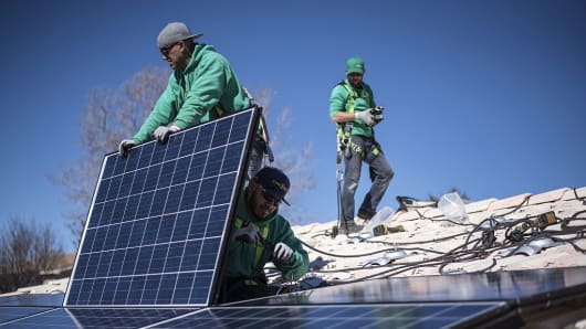 Workers secure solar panels to a rooftop during a SolarCity Corp. residential installation in Albuquerque, New Mexico.