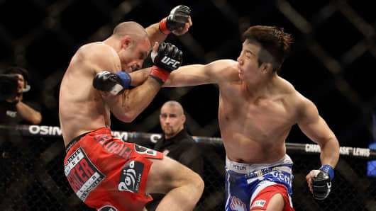 Tarec Saffiedine (L) fights Lim Hyun Gyu during the UFC Fight Night Singapore welterweight bout at Marina Bay Sands on January 4, 2014.