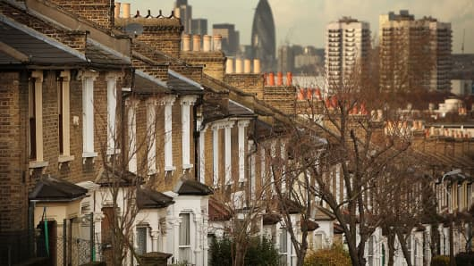 A row of houses lies in sight of Canary Wharf