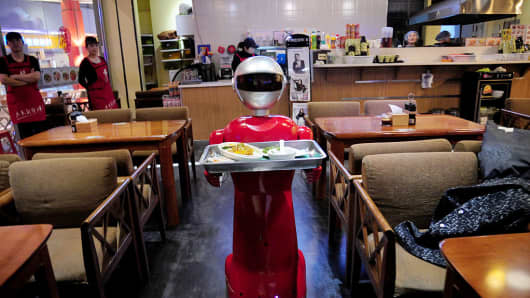 A robot delivers meals in a restaurant.