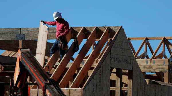 A worker stands on the roof of a home under construction at a new housing development in San Rafael, California.