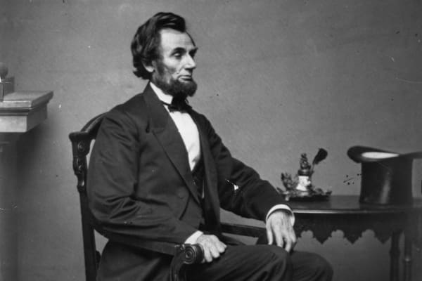 President Abraham Lincoln Sitting at a Table.